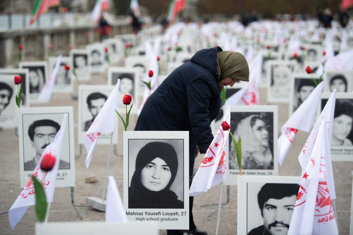 A member of the People's Mujahedin of Iran in France displays portraits of victims on the Esplanade des Invalides in Paris on October 29, 2019 to commemorate the executions of thousands of Iranian political prisoners in 1988. (AFP)
