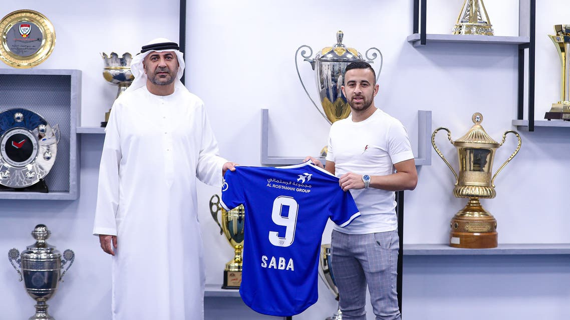 Israeli midfielder Dia Saba (R) posing with a club official during his official presentation at the al-Nasr club. (Reuters)