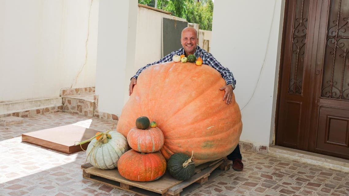 Abdul Salam Mohammad al-Mughrabi hugs his 341-kg. pumpkin that he grew at his home in Lebanon; he says the pumpkin is the largest in the Middle East. (Moe Shamseddine)