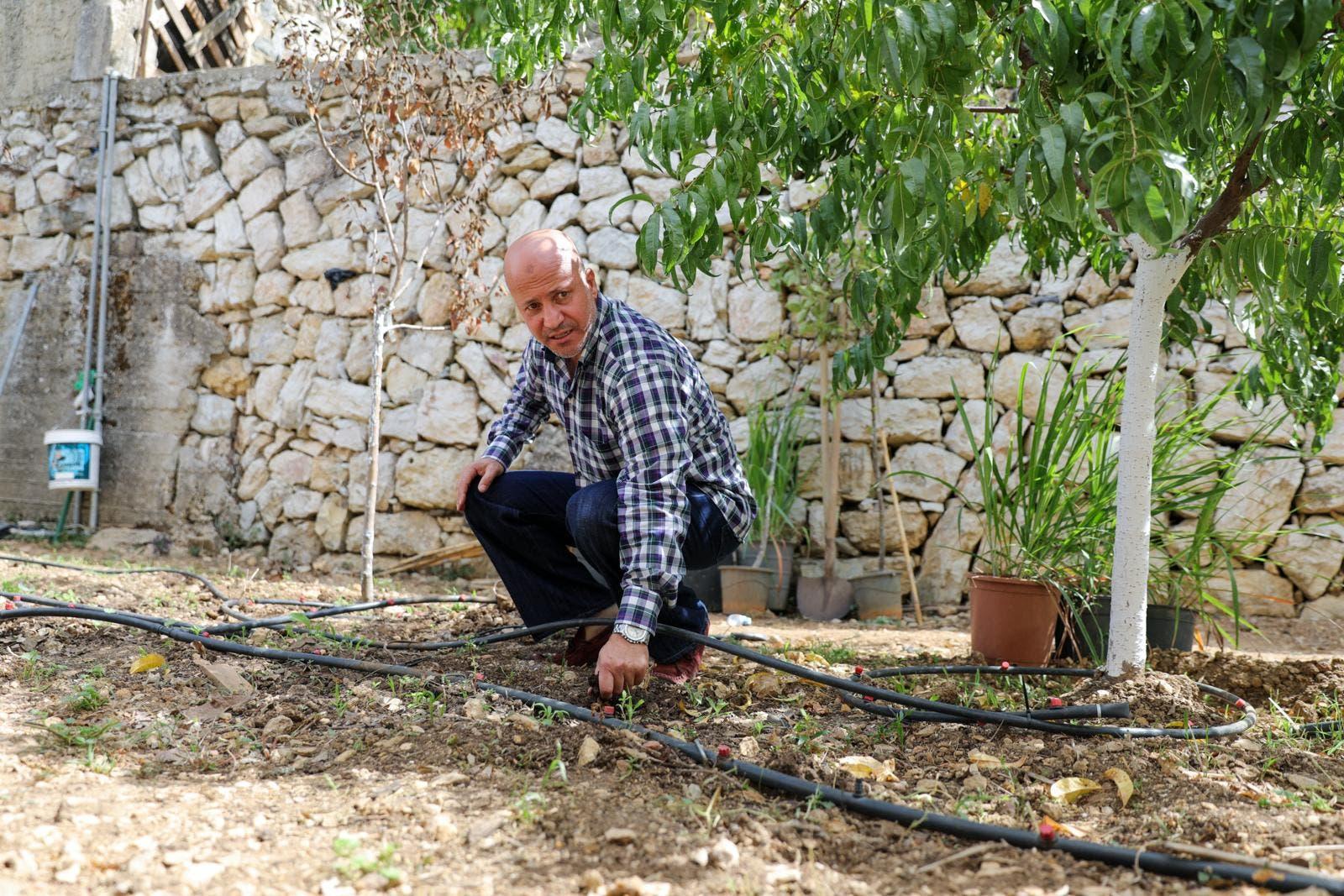 Abdul Salam Mohammad al-Mughrabi points to his irrigation system used to water his pumpkins. (Moe Shamseddine)