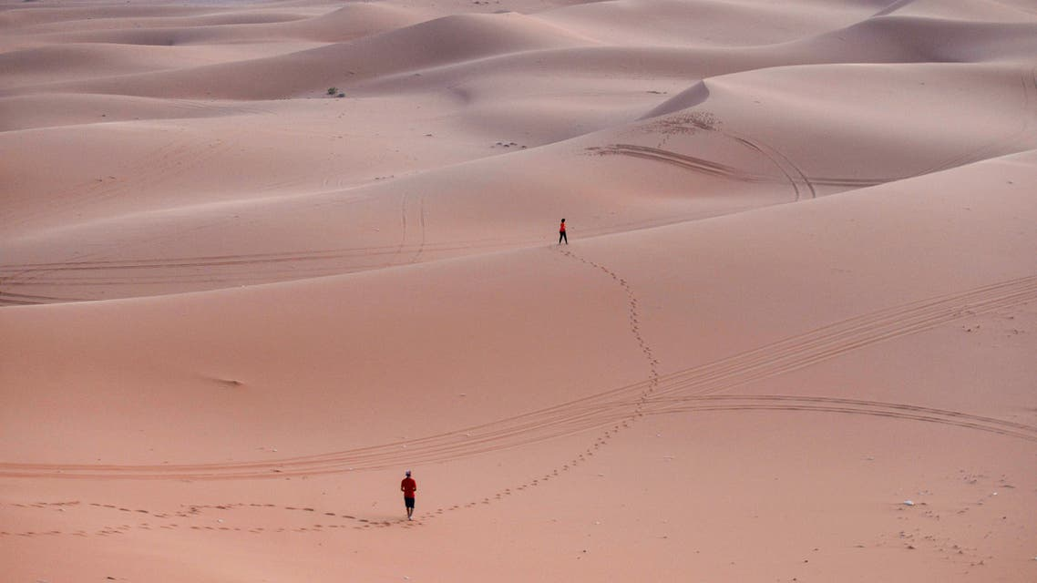 Tourists walk on the sand after surfing in the Saed desert area, 110 kilometers east of Riyadh City, on August 29, 2020.  (AFP)