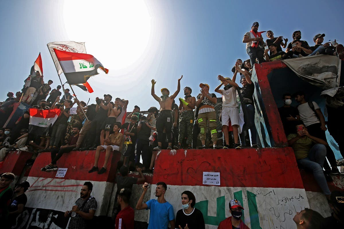Iraqi protesters chant slogans and wave the national flag during a demonstration in Tahrir Square in the center of Iraq's capital Baghdad on Oct. 1, 2020. (AFP)