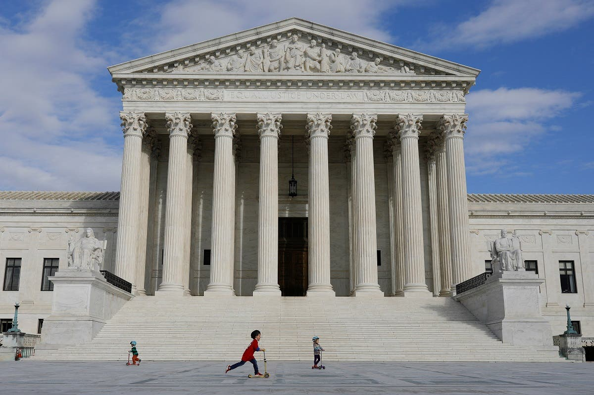 Children ride scooters across the plaza at the United States Supreme Court, in Washington, DC, March 17, 2020. (Reuters)
