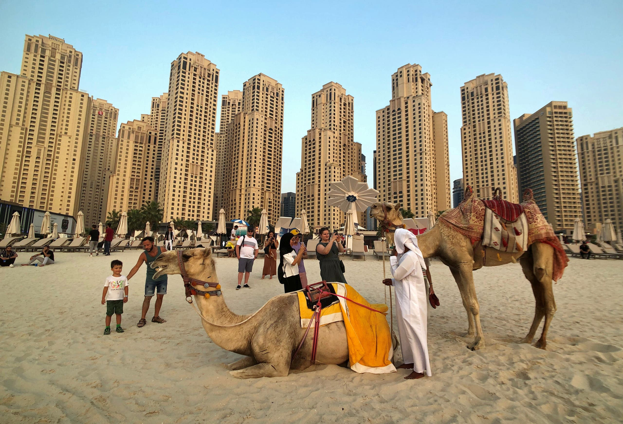 Tourists take photos with camels on the beach at Jumeirah Beach Residence in Dubai, United Arab Emirates, July 17, 2019. (AP)
