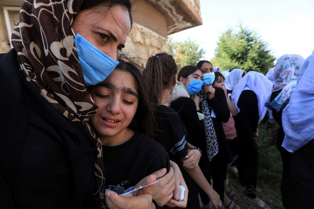 An Iraqi Yazidi woman comforts a grieving youngster during the funeral of Baba Sheikh Khurto Hajji Ismail (image), supreme spiritual leader of the Yazidi religious minority. (AFP)