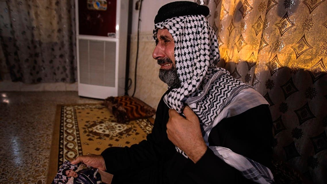 Jasb Hattab Aboud, father of the kidnapped protester Ali Jasb, cries as he holds his son's picture in his home un the town of Amara,Iraq. (AP)