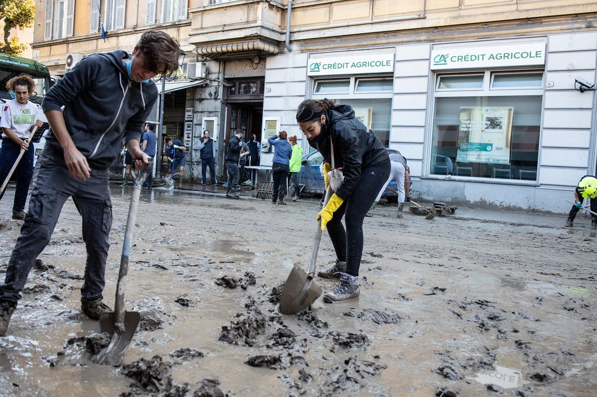 People clean the mud in Ventimiglia, Italy on October 3, 2020 after the Roya river flooded overnight, submerging the whole city with water and mud. (AFP)