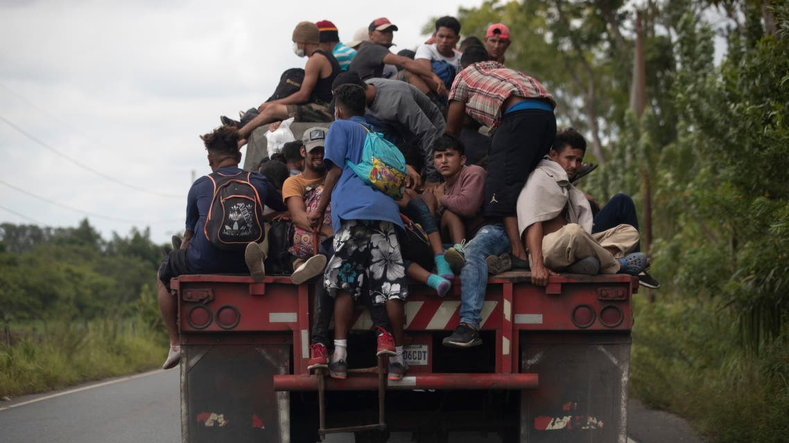 Migrants ride on the back of a freight truck that slowed down to give them an opportunity to jump on in Rio Dulce, Guatemala, Friday, Oct. 2, 2020. (AP)