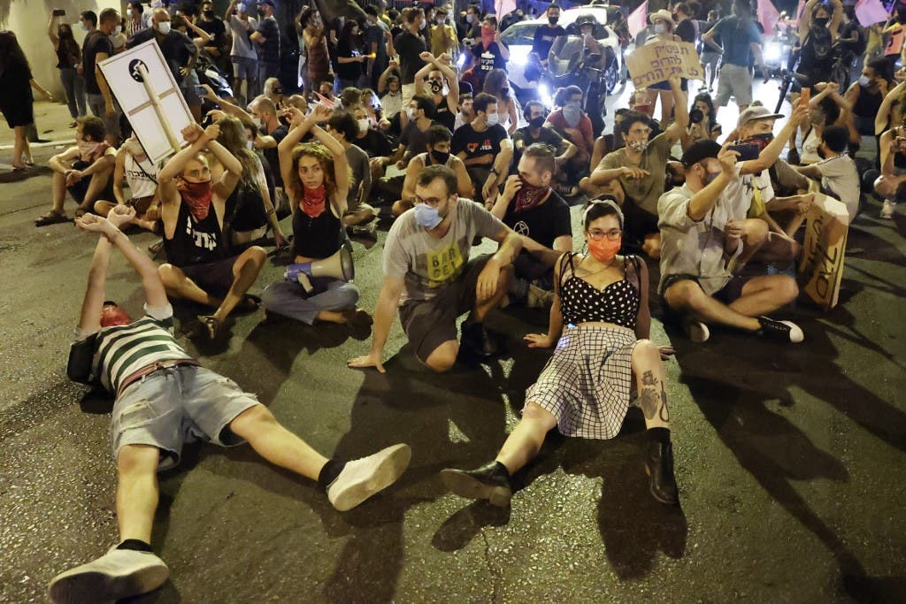 Israeli protesters sit on the ground during a demonstration against the Israeli prime minister and against the second nationwide lockdown imposed by the government in a bid to stem the increase of coronavirus cases, in Tel Aviv, October 1, 2020. (AFP)