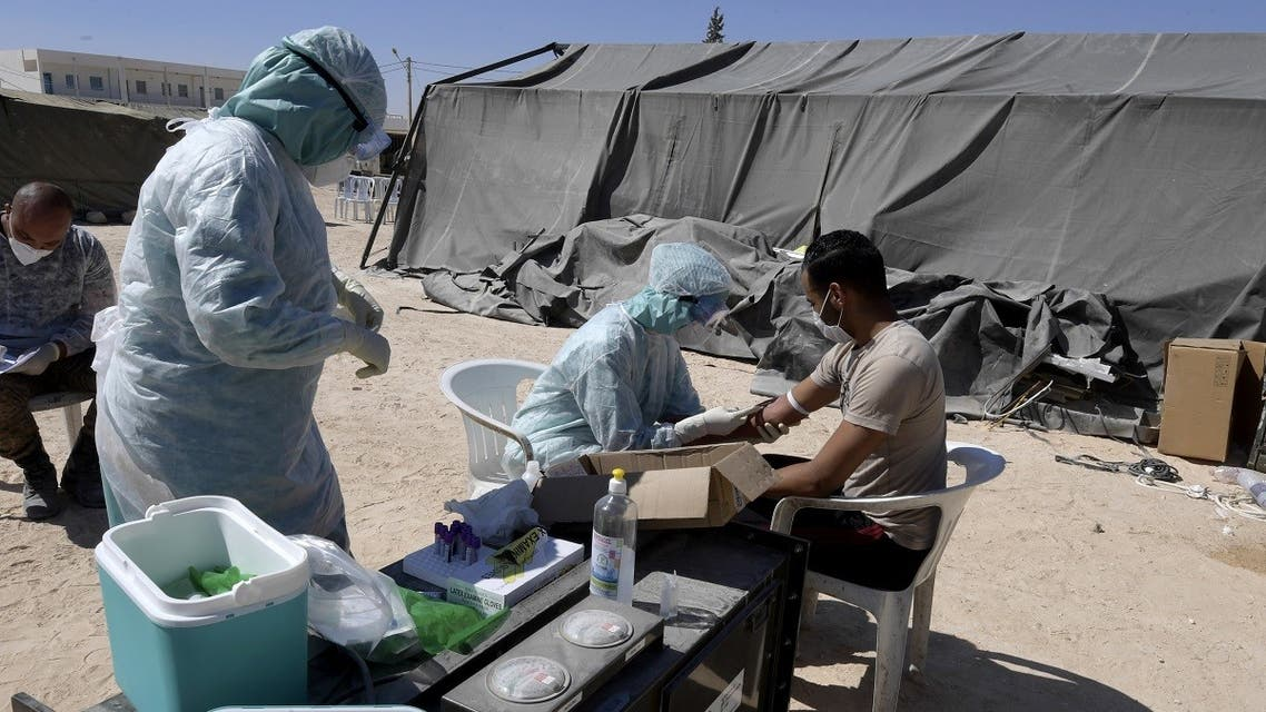 A nurse takes a blood sample from a man before a covid-19 test at a military hospital in the town of El-Hamma, in Tunisia's southwestern Gabes governorate, August 26, 2020. (AFP)