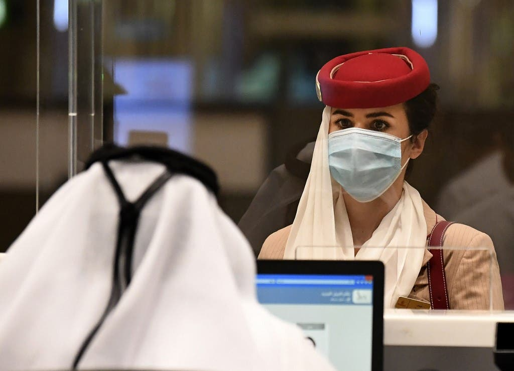 A stewardess of an Emirates Airlines flight from London arrives at Dubai International Airport on May 8, 2020 amid the coronavirus Covid-19 pandemic. (AFP)