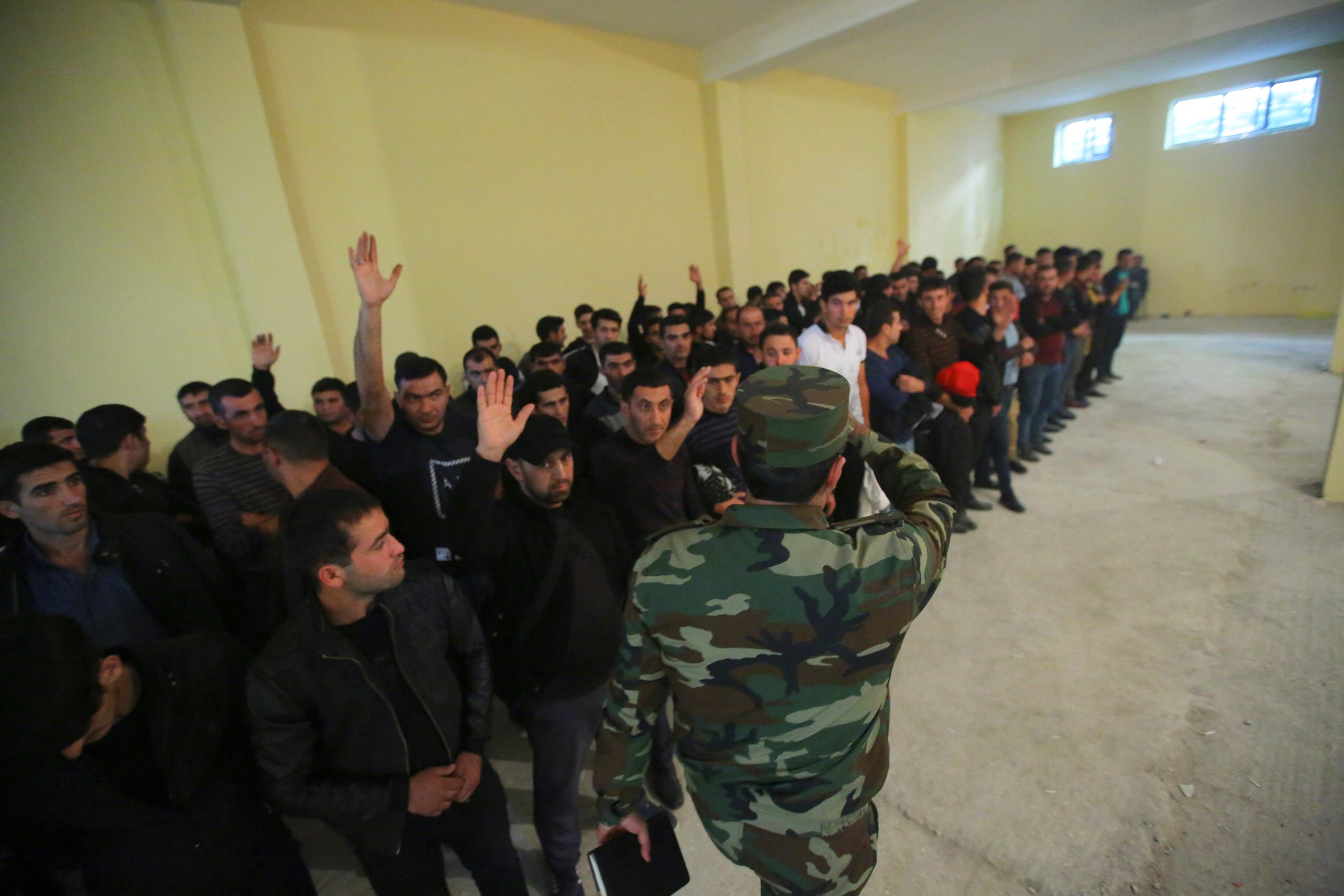 Azerbaijani men gather in a military commissariat to join the army in Tartar region, Azerbaijan on Sept. 30, 2020.  (AP)