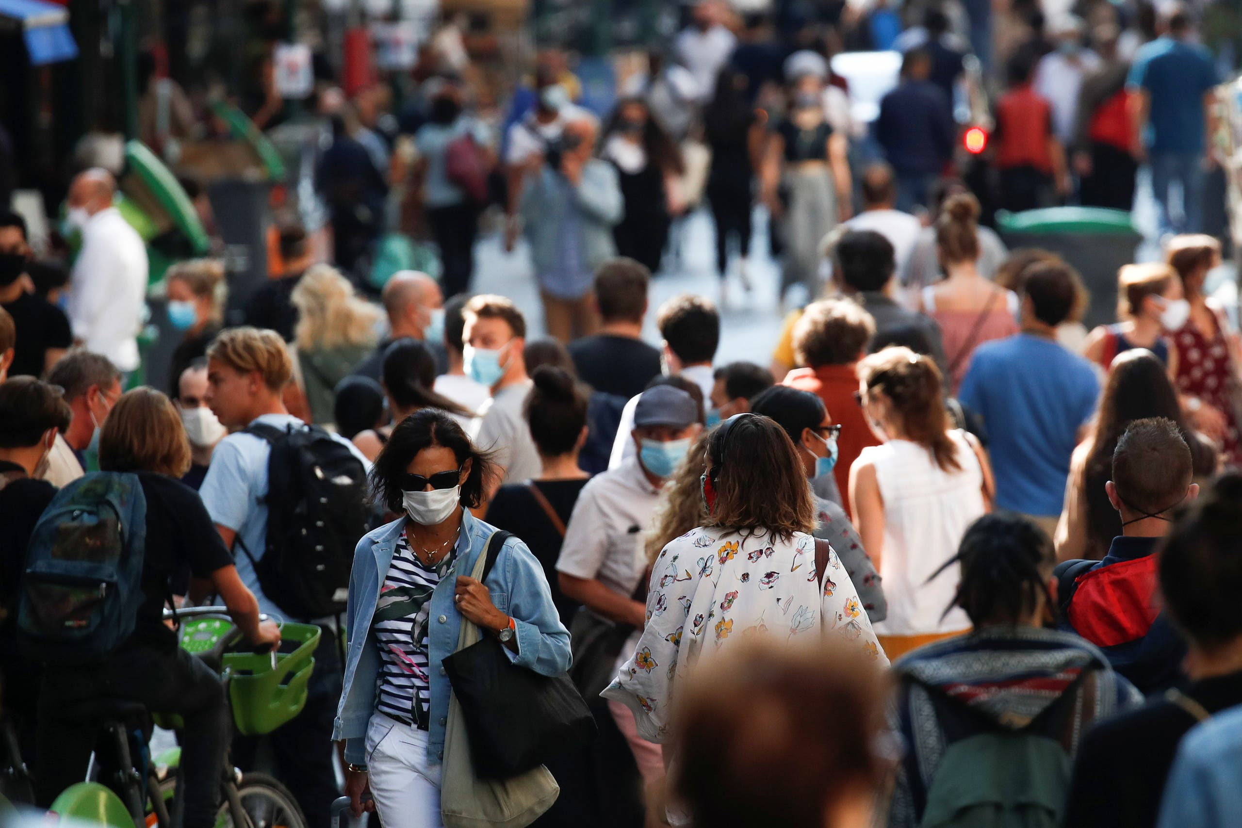 People wearing protective face masks walk in a busy street in Paris. (File photo: Reuters)