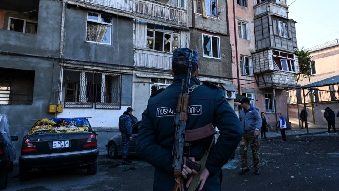 A police officer stands in front of an apartment building that was supposedly damaged by recent shelling in the breakaway Nagorno-Karabakh region's main city of Stepanakert on October 3, 2020, during the ongoing fighting between Armenia and Azerbaijan over the disputed region. (AFP)
