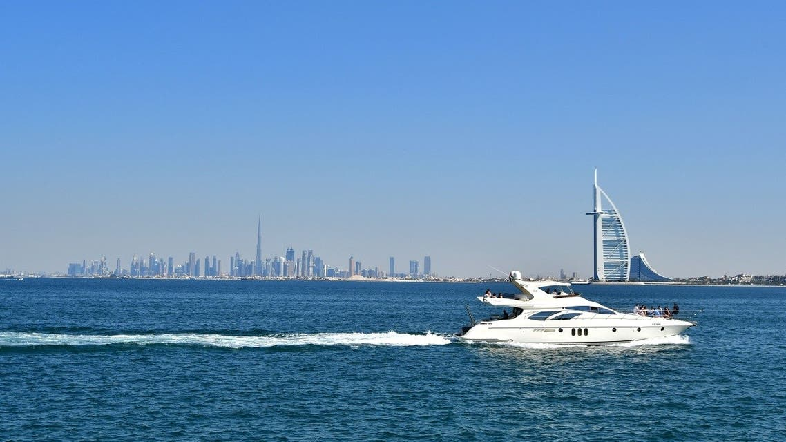 This picture taken on February 8, 2019, shows a yacht with the Burj al-Arab (R) in the foreground and Burj Khalifa (L) in the background. (Giuseppe Cacace/AFP)