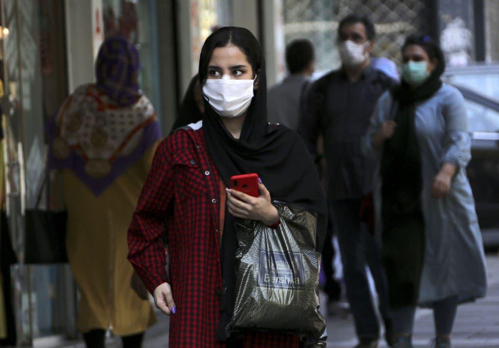 A woman, mask-clad as a COVID-19 coronavirus pandemic precaution, walks past shops along a street in Iran's capital Tehran on September 27, 2020. (AFP)
