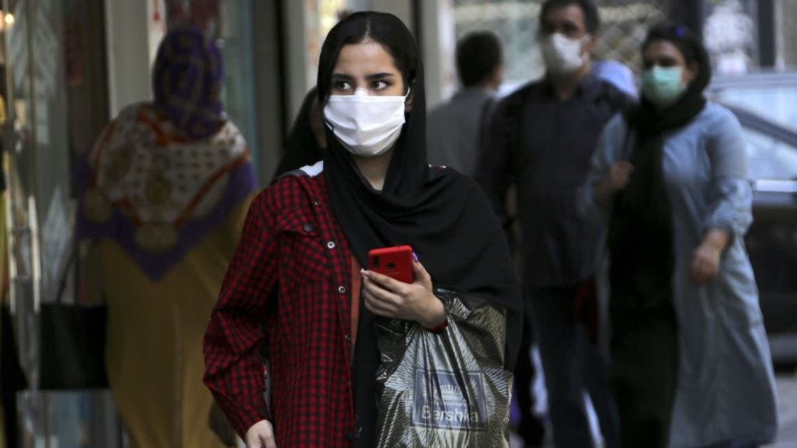 A woman, mask-clad as a COVID-19 coronavirus pandemic precaution, walks past shops along a street in Iran's capital Tehran on September 27, 2020. (AFP)