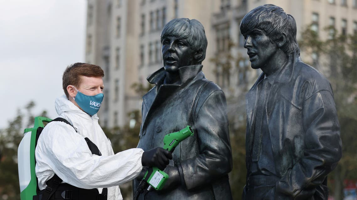 A man disinfects a statue of the Beatles amid the outbreak of the coronavirus disease (COVID-19), in Liverpool, Britain October 1, 2020. (Reuters)