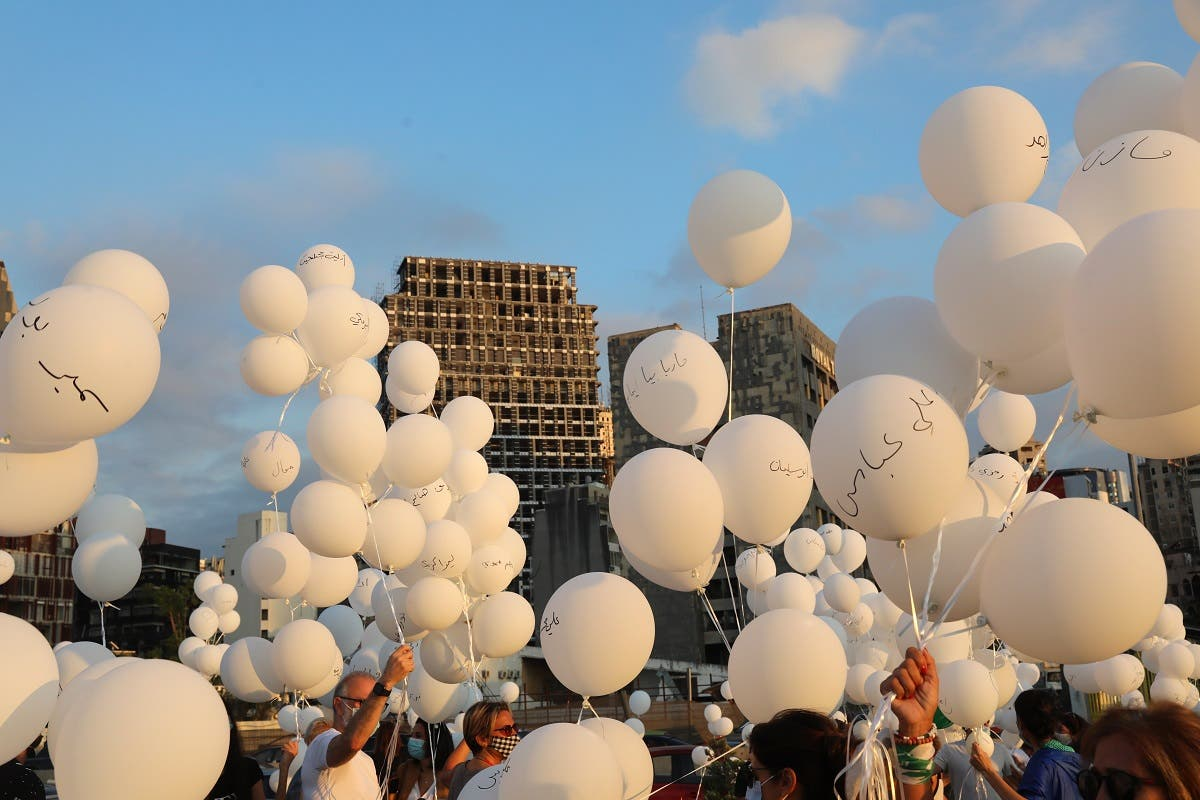 People gather to release white balloons near the seaport of Beirut on October 4, 2020, to commemorate the second month after the August 4 massive explosion. (AFP)