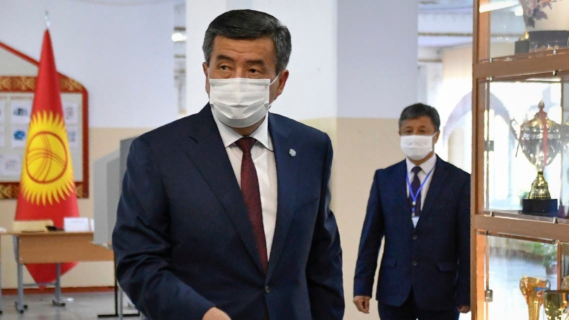 Kyrgyz President Sooronbay Jeenbekov wearing a face mask casts his ballot at a polling station during parliamentary election in Bishkek on October 4, 2020, amid the ongoing coronavirus pandemic. (Vladimir Voronin/Pool/ AFP)