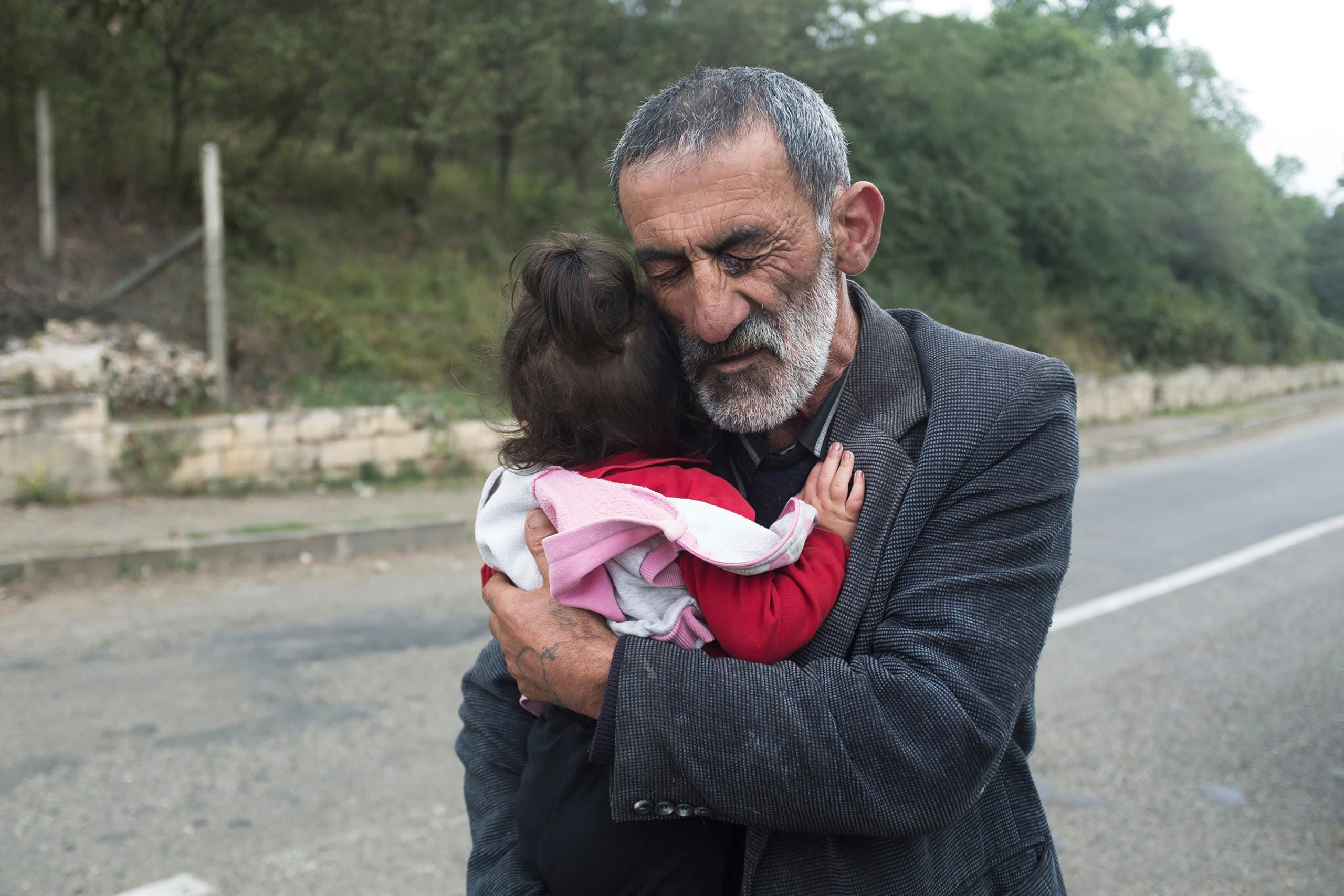 A local resident holds his granddaughter in the Hadrut province of Nagorno-Karabakh on Oct. 1, 2020. (AP)