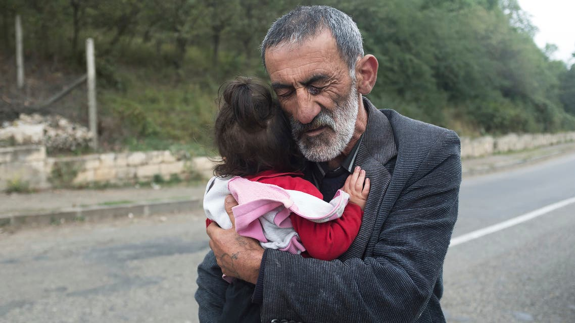 A local resident holds his granddaughter in the Hadrut province of self-proclaimed Republic of Nagorno-Karabakh, Azerbaijan on Oct. 1, 2020. (AP)