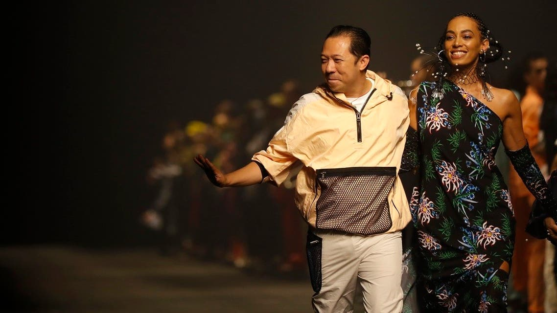 Designer Kenzo Takada, left, accepts applause as he walks with singer Solange Knowles after the Kenzo mens Spring-Summer 2020 fashion collection presented in Paris, Sunday, June 23 2019. (AP Photo/Michel Euler)
