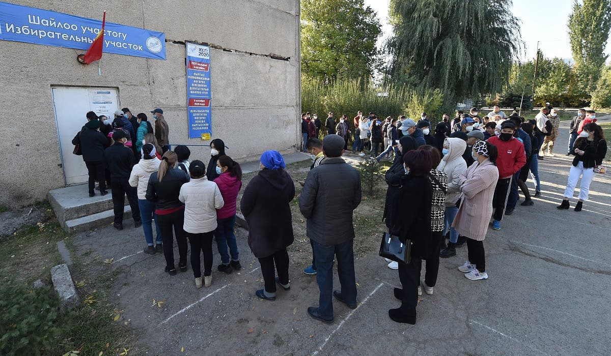 People queue outside a polling station during Kyrgyzstan's parliamentary election in the village of Besh-Kungey outside Bishkek on October 4, 2020, amid the ongoing coronavirus pandemic.  (Vyacheslav Oseledko/AFP)