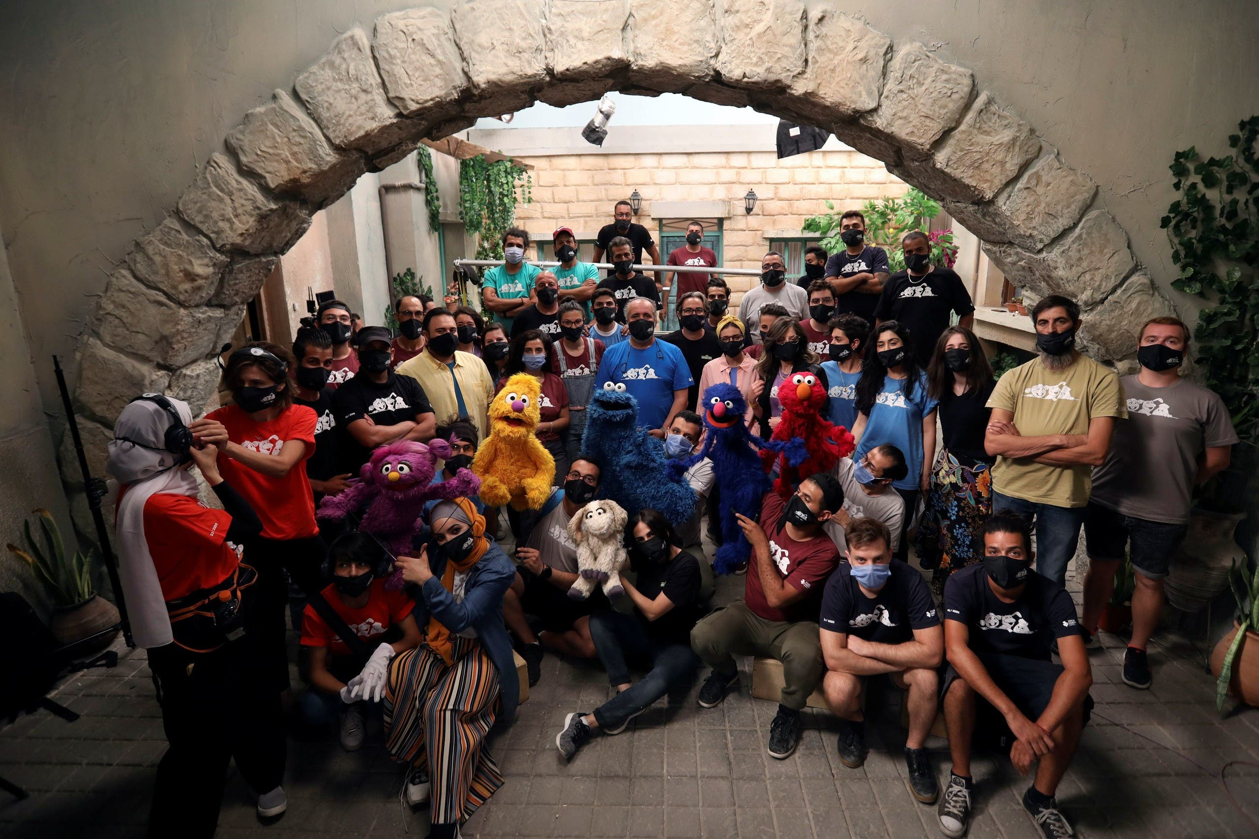 The staff of the children program Ahlan Simsim pose for a group picture with their puppets during the filming of a scene on the set of the show in a studio in Amman, Jordan. (Reuters)
