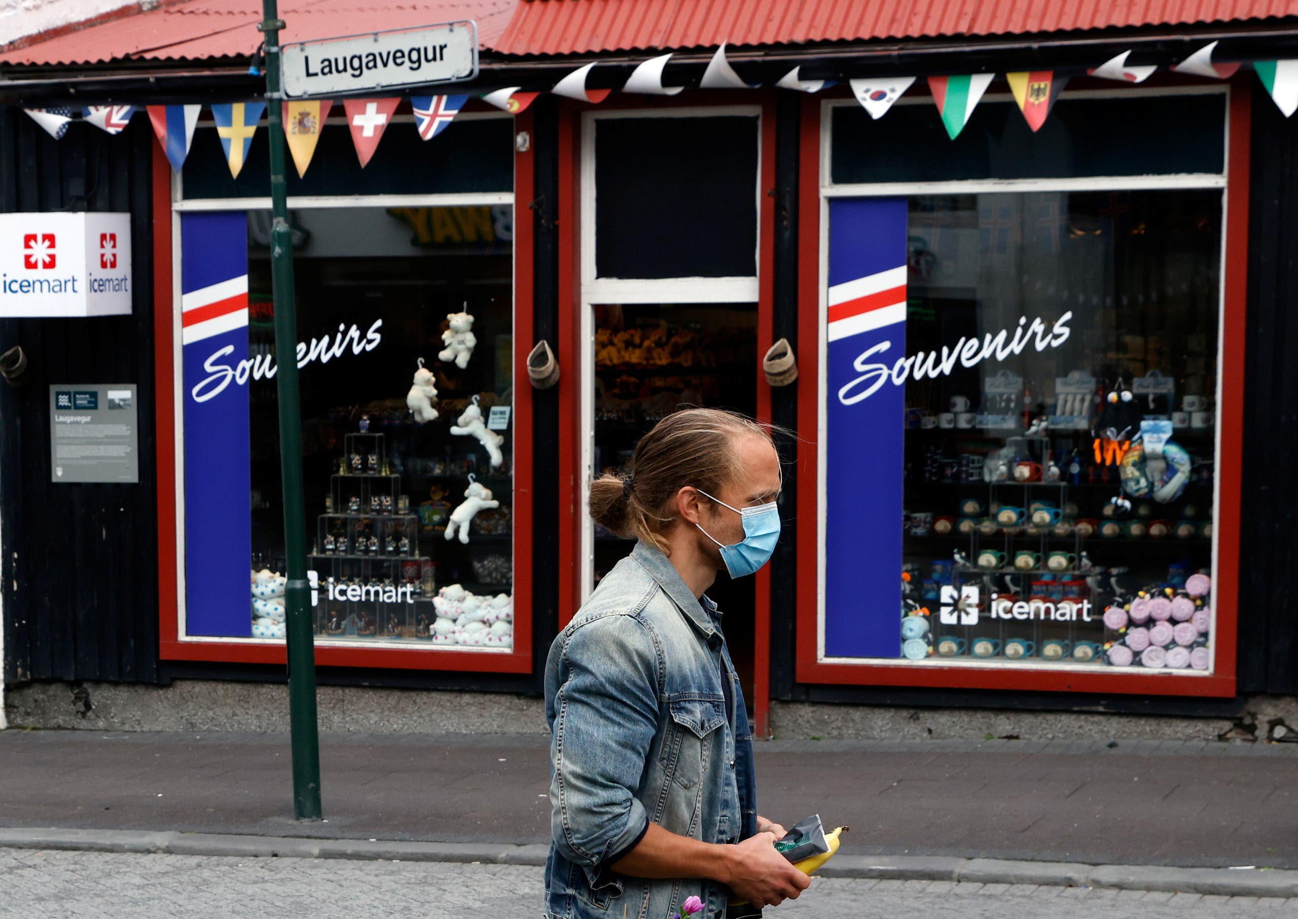 A man with a face mask walks past a tourist shop as the outbreak of the coronavirus disease (COVID-19) continues in Reykjavik, Iceland, September 3, 2020. (Reuters)