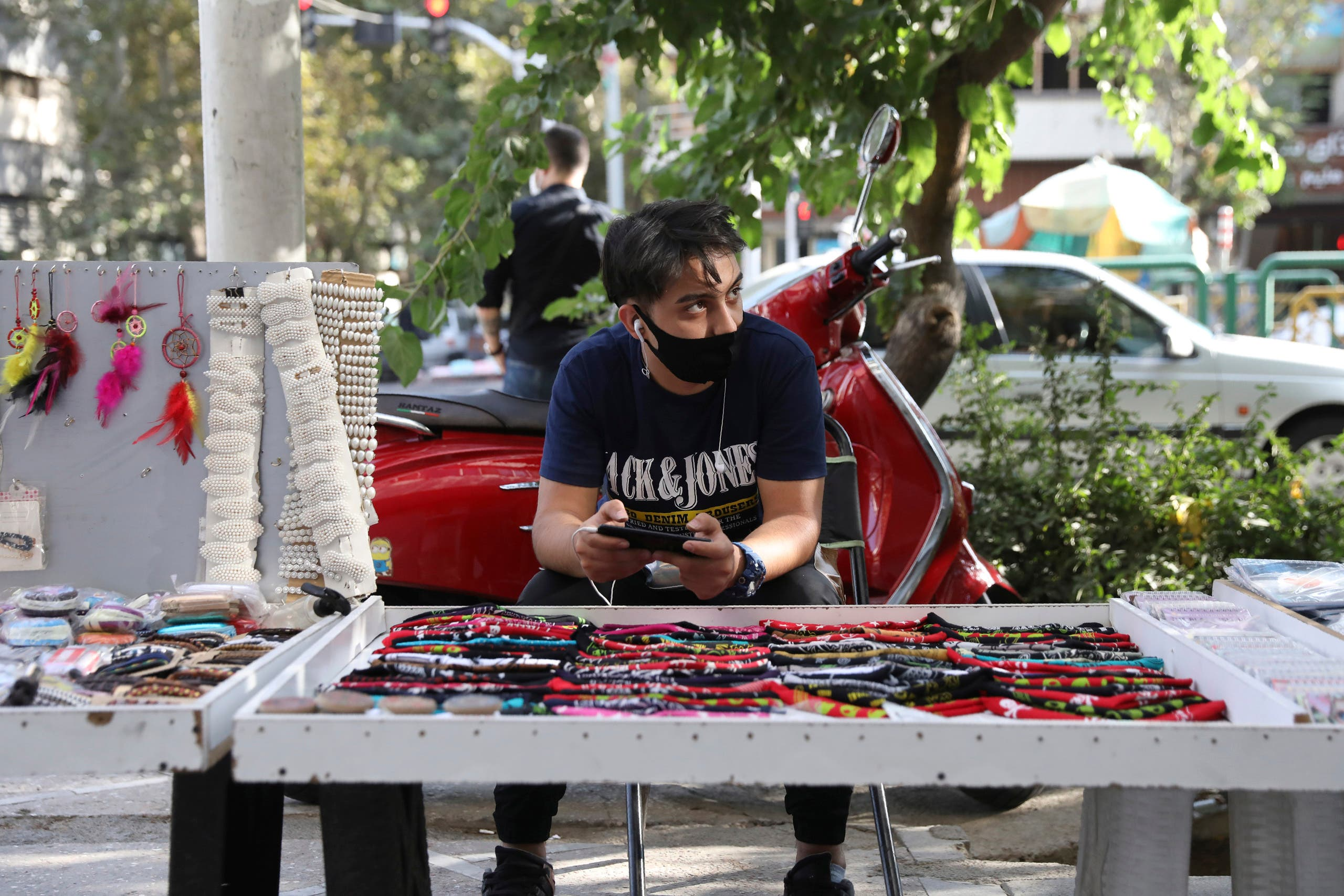A street vendor wearing a protective face mask to help prevent the spread of the coronavirus in downtown Tehran on Sept. 20, 2020. (AP)