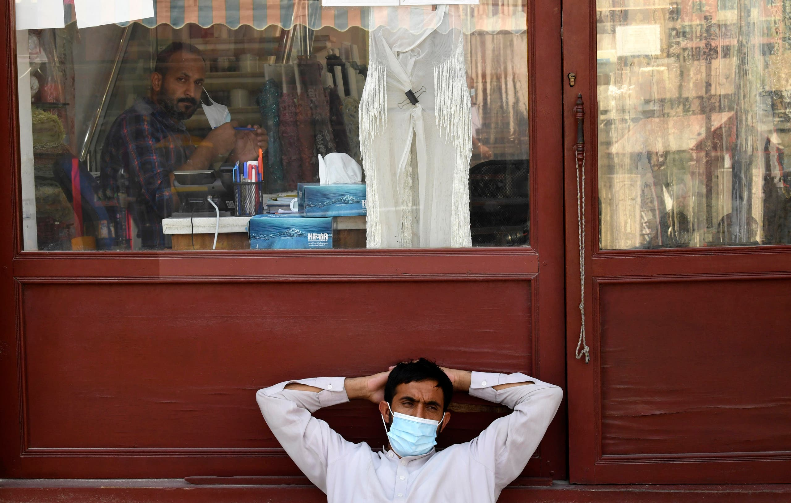 A man sits in front of a tailor's shop at the Deira Souk in the Emirati city of Dubai on September 30, 2020. (AFP)