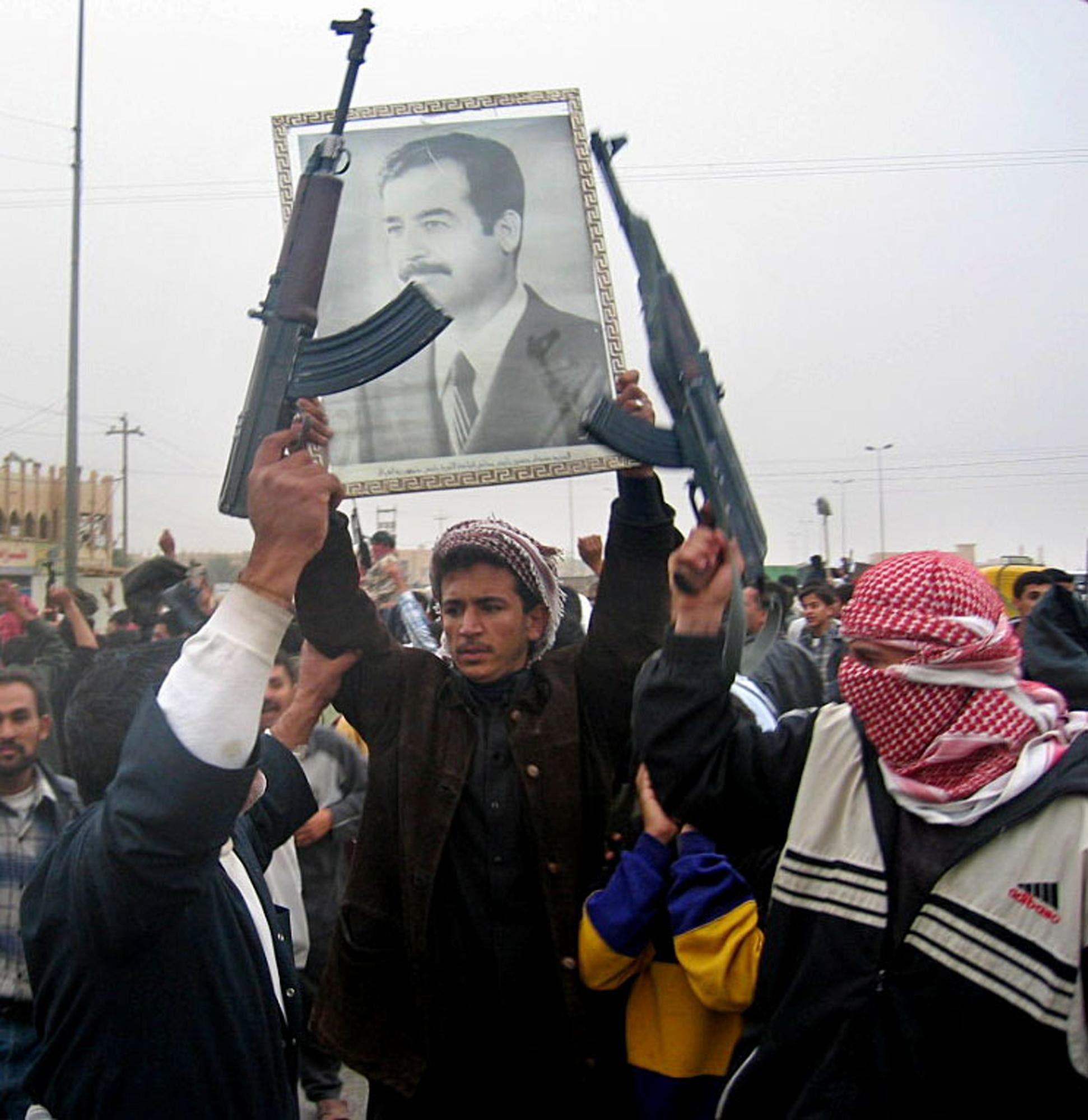 """Several hundred armed demonstrators and local residents take to the streets of the town of Fallujah, 50 kms west of Baghdad, 16 December, 2003, chanting pro-Saddam slogans and letting off celebratory gunfire into the air, pledging their allegiance to their deposed leader, and chanting, """"We will sacrifice ourselves to you Saddam, with our blood, with our soul."""" (AFP)"""