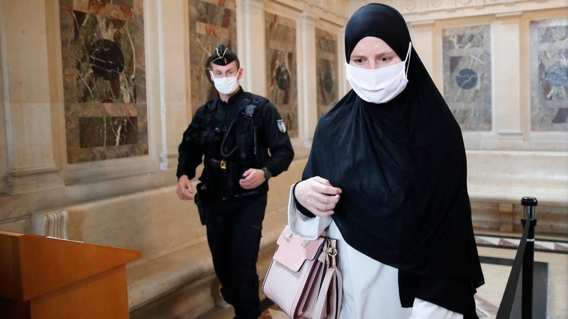 A police officer watches a woman being checked during the trial of a 29-year-old Algerian man accused of killing a woman and trying to blow up a church near Paris, a failed 2015 attack that investigators say was orchestrated by Islamic State extremists in Syria, on October 5, 2020, in Paris. (AP)