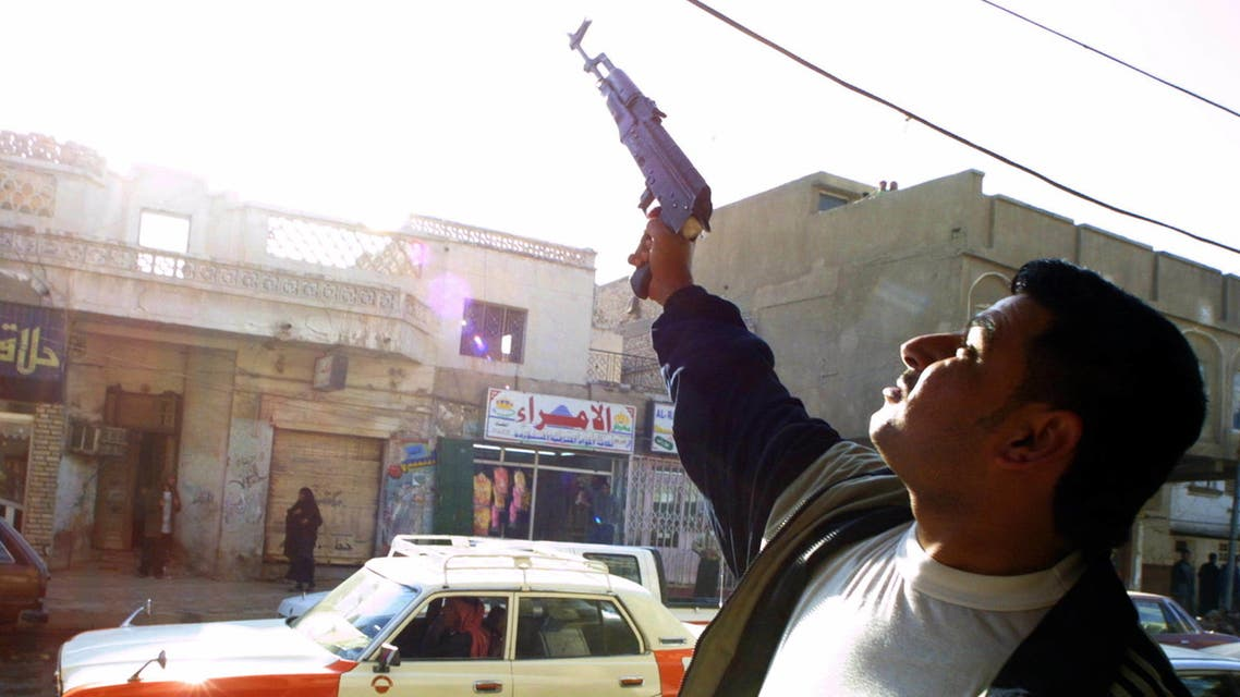 An Iraqi shoots celebratory gunfire in the southern city of Nasiriyah after the capture of ousted Iraqi leader Saddam Hussein in his hometown of Tikrit 14 December 2003. (AFP)