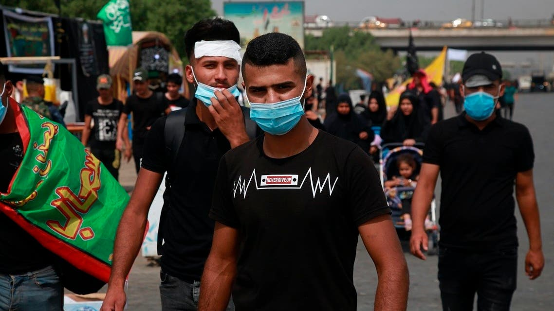 Shia pilgrims wearing face masks as a precaution against the coronavirus while marching to the holy shrines of Imam Hussein and Imam Abbas ahead of the Arbaeen festival in Karbala. (AP)
