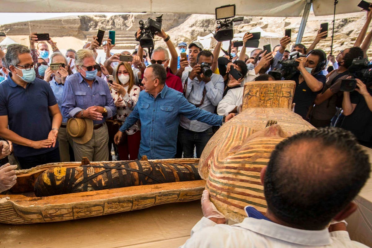 A picture taken on October 3, 2020 shows Egyptian actor Hussein Fahmy (2nd-L) look on as Egyptian Minister of Tourism and Antiquities Khaled Al-Anani (L), and Mustafa Waziri (R), Secretary General of the Supreme Council of Antiquities, unveil the mummy inside a sarcophagus excavated by the Egyptian archaeological mission working at the Saqqara necropolis. (AFP)