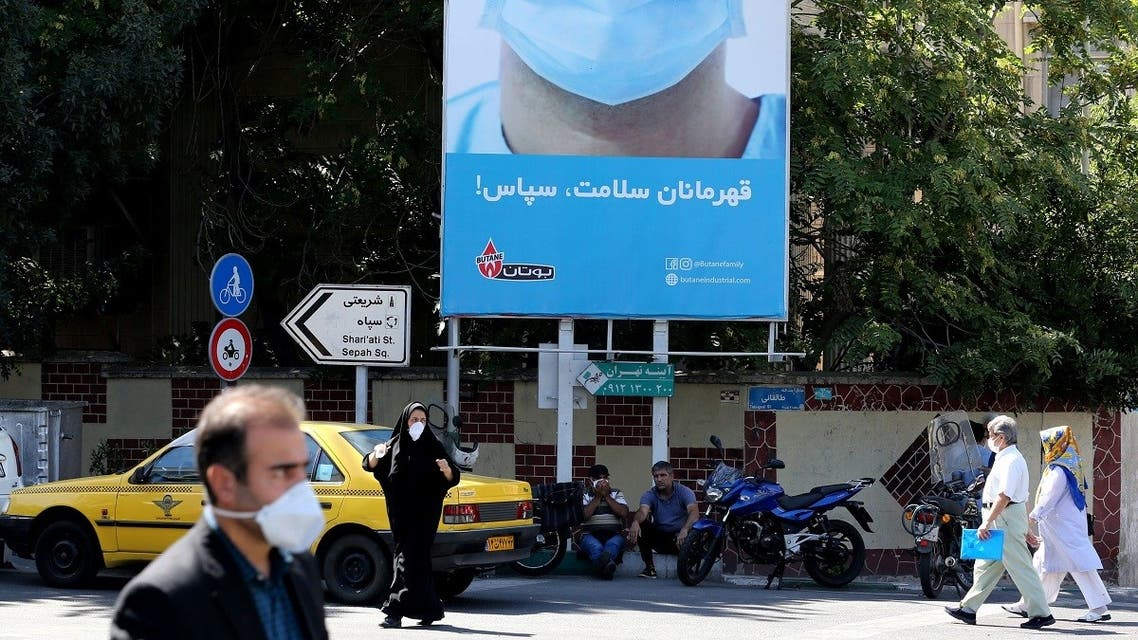 Iranians, wearing protective face masks, walk under a billboard thanking first responders in the capital Tehran on July 22, 2020, during coronavirus pandemic. (Atta Kenare/AFP)