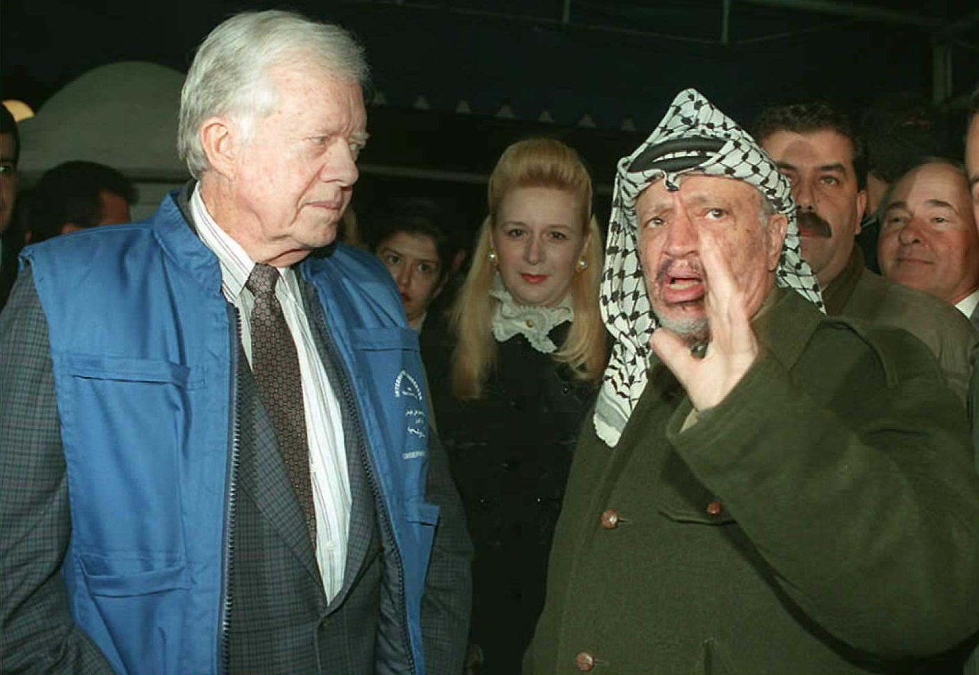 Former US President Jimmy Carter (L) watches Palestinian leader Yasser Arafat speak to reporters  upon his arrival in Gaza City, January 19, 1996. (File photo, AFP)