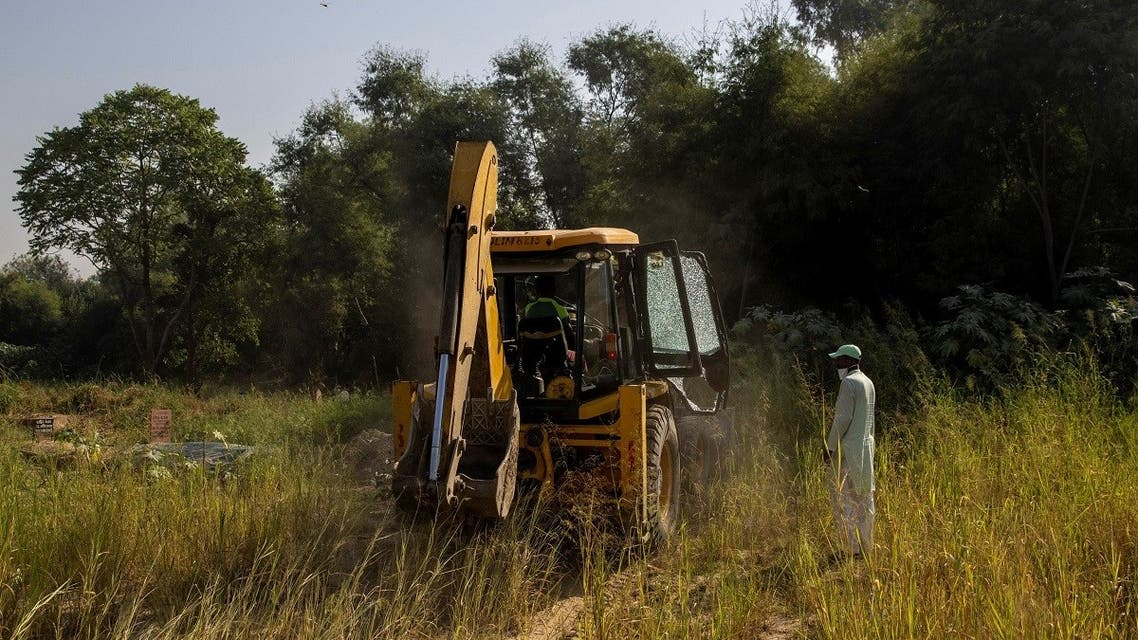 Mohammad Shameem, a 38-year-old grave digger, guides an excavator as it clears an area for a new burial site. (Reuters)