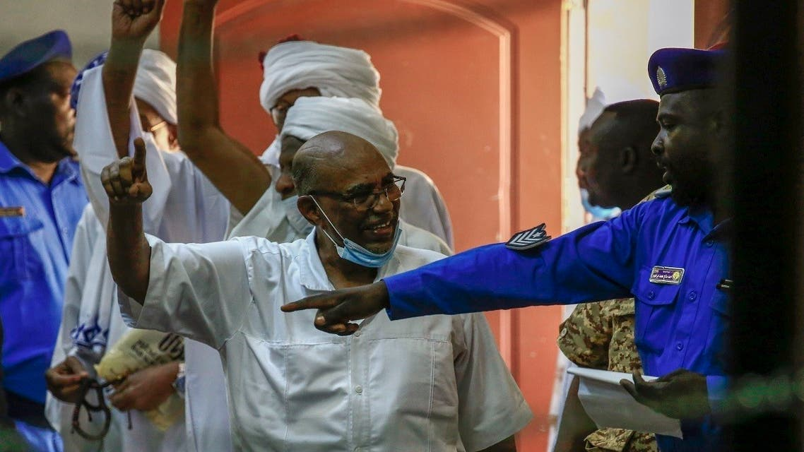 Sudan's ousted president Omar al-Bashir (C) speaks to a police officer as he arrives for his trial in the capital Khartoum, on October 6, 2020. (AFP)