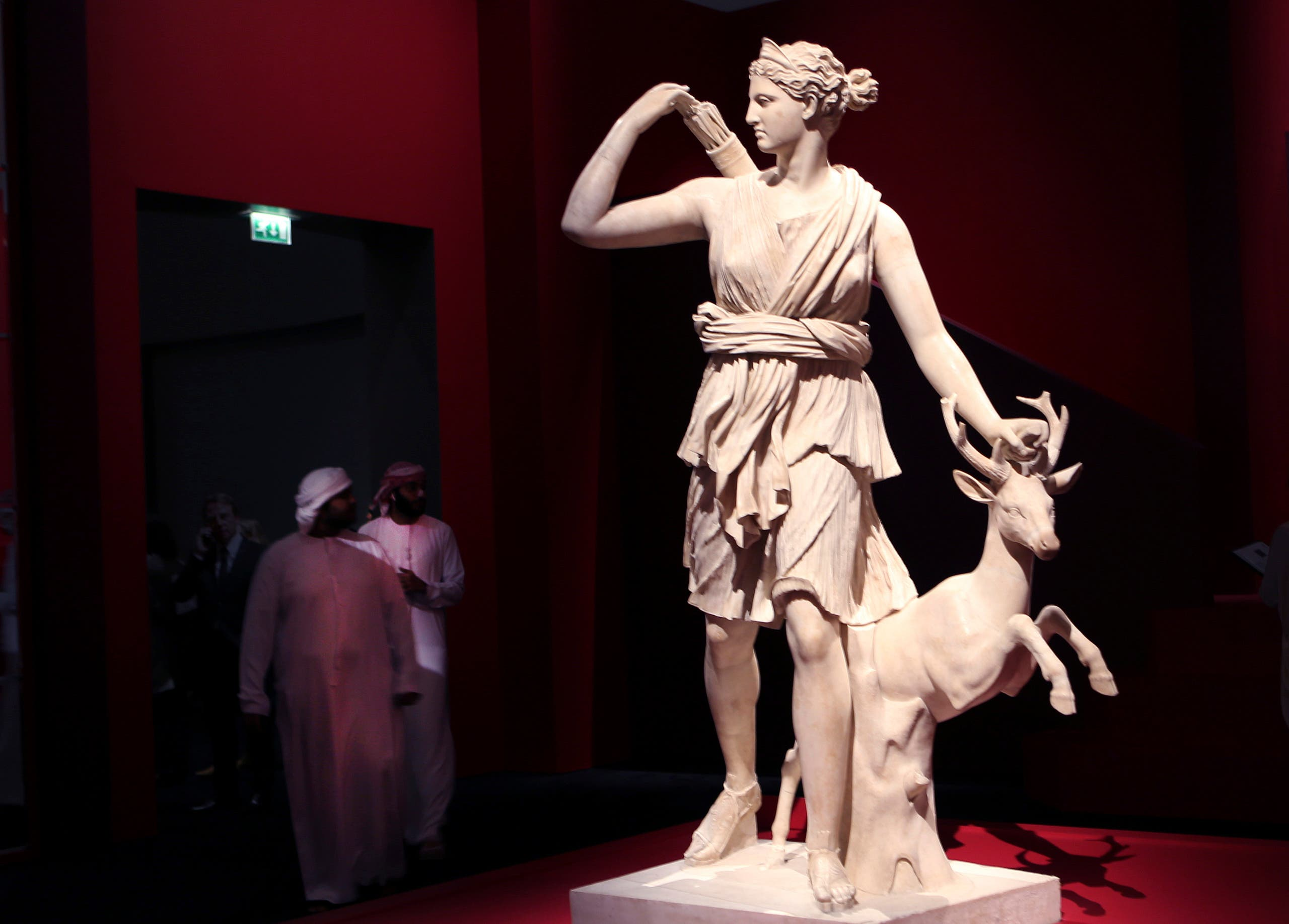 Emirati men passe by the The Diana of Versailles or Artemis of the hunter sculpture, Italy, 2nd Century CE, at the Louvre Museum in Abu Dhabi, United Arab Emirates, Tuesday, Dec. 19, 2017. (AP)