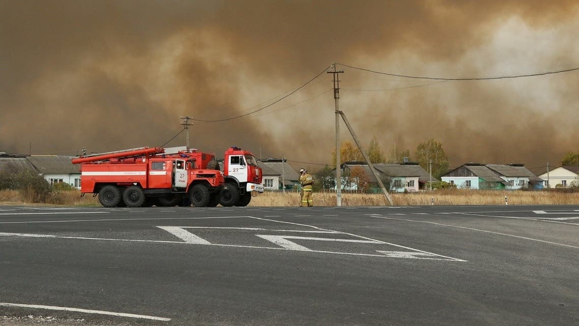 Fire trucks are seen on the road as smoke rises from the site of a fire at an ammunition depot in Ryazan Region, Russia Oct. 7, 2020. (Reuters)