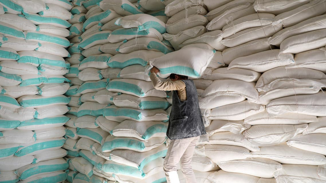 Workers handle sacks of wheat flour at a World Food Programme food aid distribution center in Sanaa. (Reuters)
