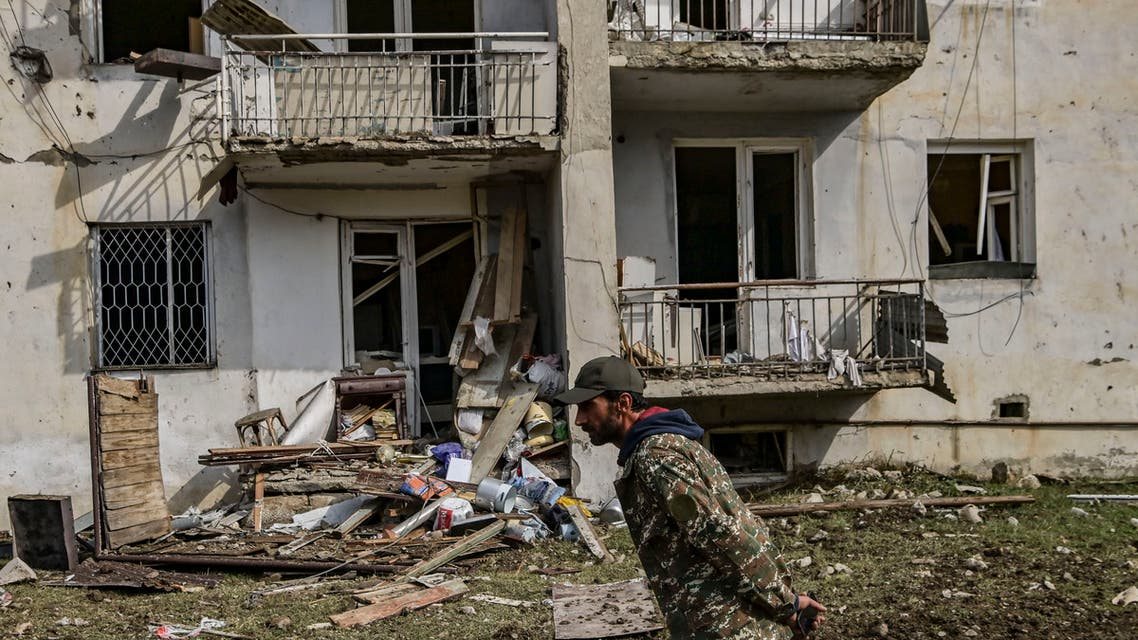 A man walks in front of a destroyed house after a late October 7th sheling in the breakaway Nagorno-Karabakh region's main city of Stepanakert. (AFP)