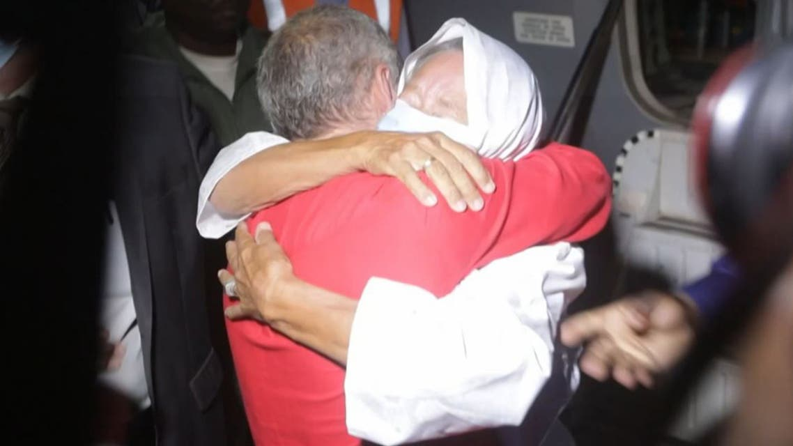 This video frame grab from an AFP video from October 8, 2020, shows French ex-hostage Sophie Petronin (R), who was released and flew to Bamako, hugging her son Sebastien Petronin (L) after she was reunited with him. (AFP)