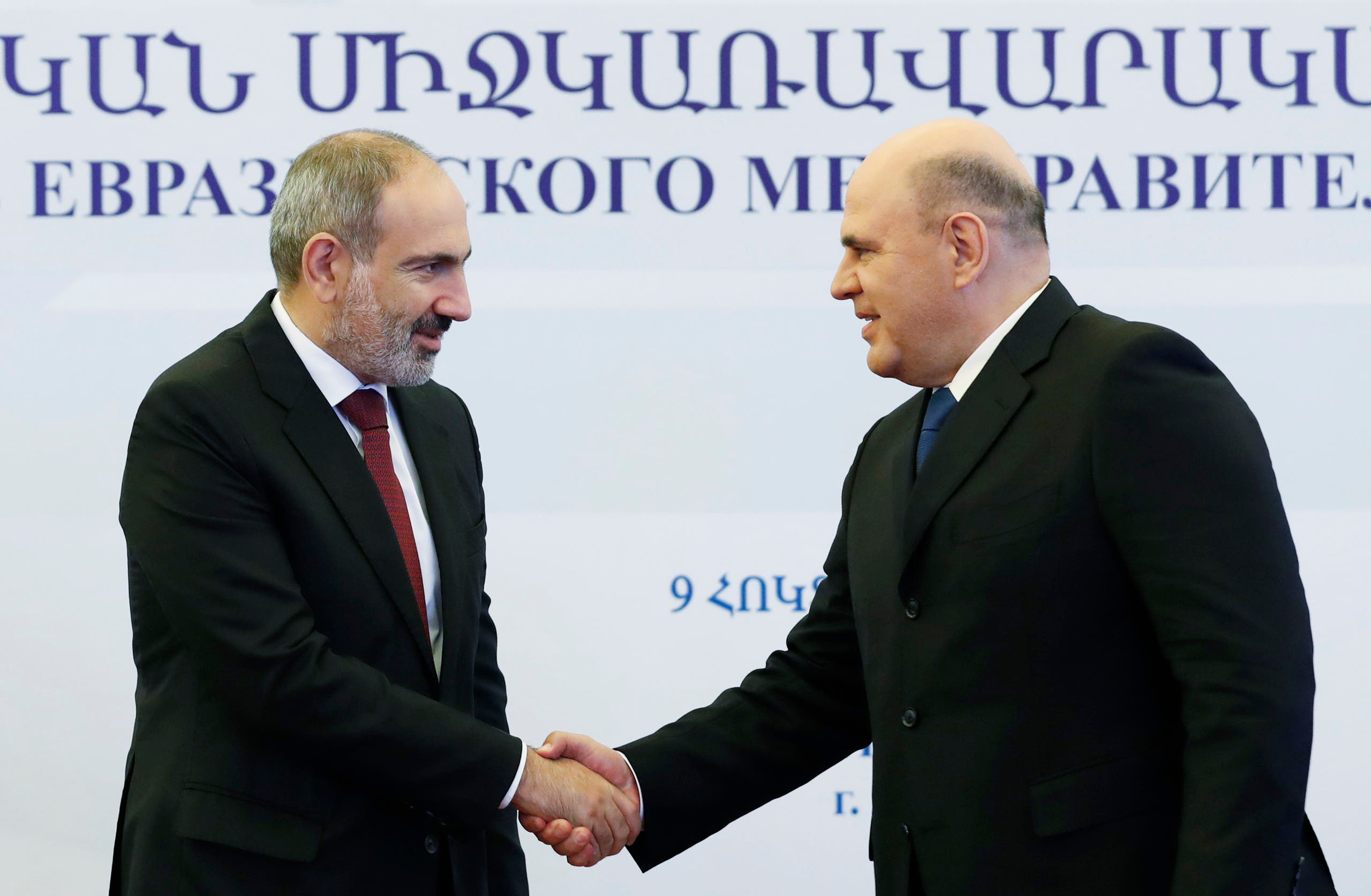 Armenian Prime Minister Nikol Pashinyan (L) shakes hands with Russian Prime Minister Mikhail Mishustin during a meeting of the Eurasian Economic Union's (EAEU) intergovernmental council in Yerevan, on October 9, 2020. (AFP)