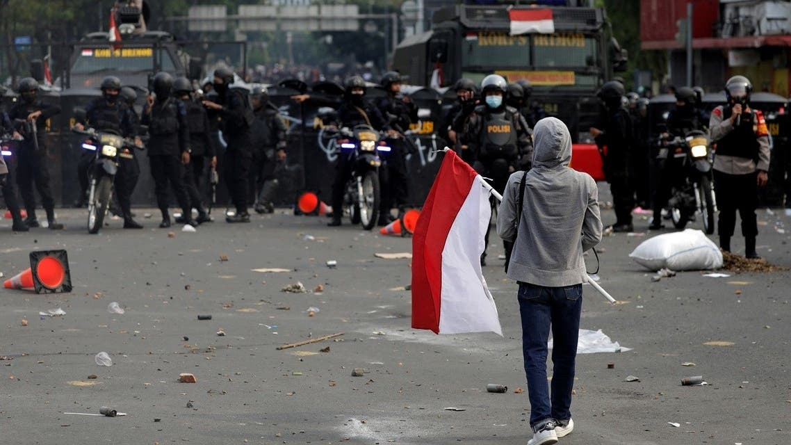 A demonstrator holds an Indonesian flag during a protest against the government's labour reforms in a controversial jobs creation law in Jakarta, Indonesia, on October 8, 2020. (Reuters)