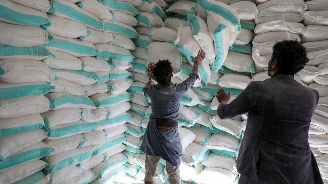 Workers handle sacks of wheat flour at a World Food Programme food aid distribution center in Sanaa. (File photo: Reuters)