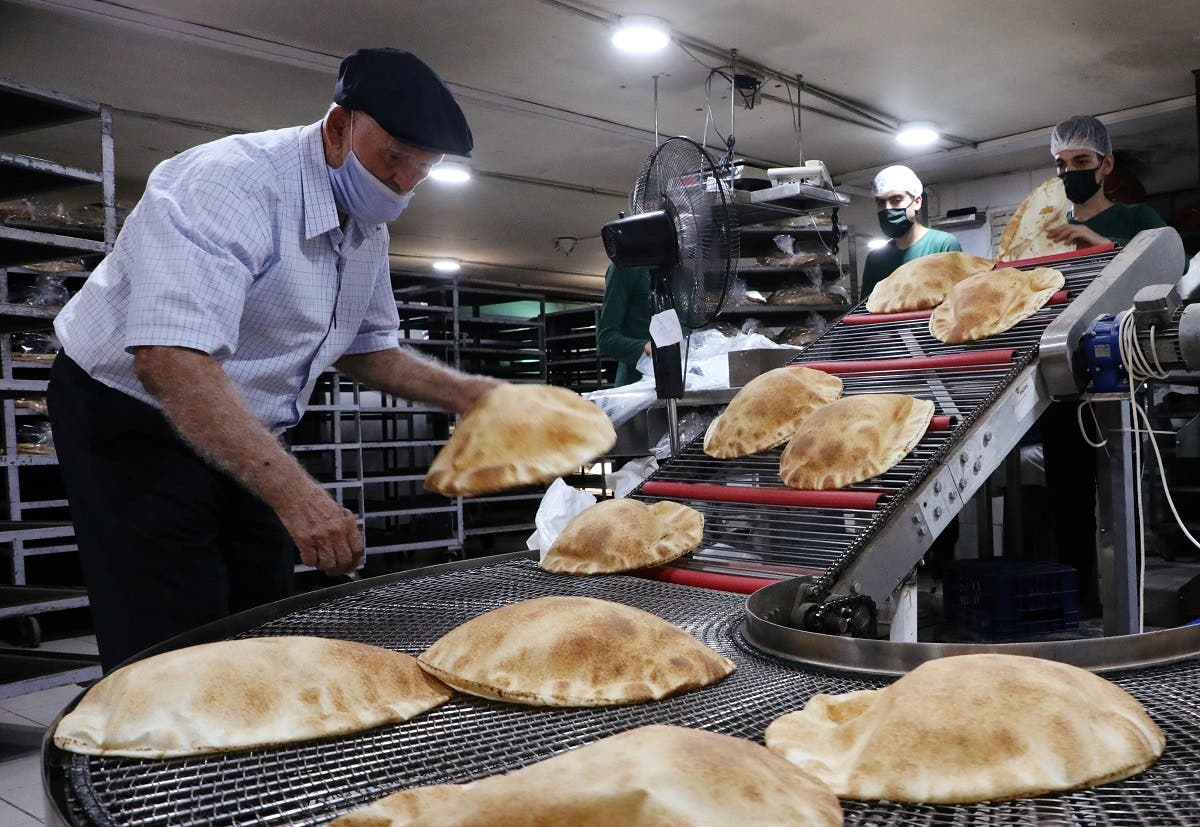 Workers wearing protective masks prepare baked breads inside a bakery in Beirut, Oct. 8, 2020. (Reuters)